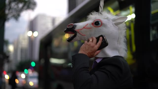 Business man with Unicorn Mask talking on the mobile at city video