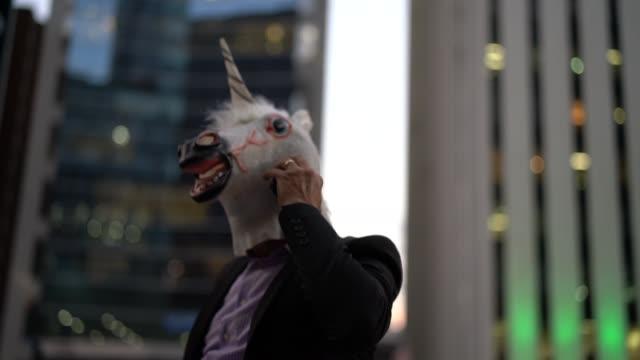 Geschäftsmann mit Einhorn Maske sprechen auf dem Handy bei city – Video