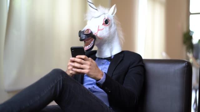 Geschäftsmann mit Einhorn Maske verwenden Mobile Büro – Video