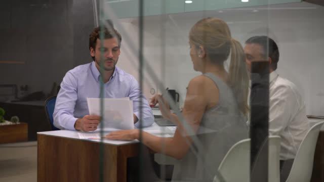 문서에서 가리키는 동안 뭔가 대해 그의 동료와 회의에서 비즈니스 관리자 - 이성 커플 스톡 비디오 및 b-롤 화면