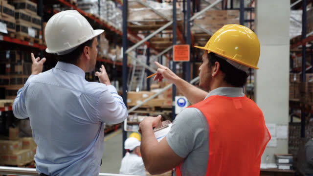 Business manager instructing male warehouse supervisor while pointing out at different shelfs video