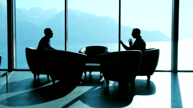 business manger having a job interview with future sales employee. finance economy growth concept background silhouette of two business men having a business meeting in modern office lobby hall at sunset light face to face stock videos & royalty-free footage