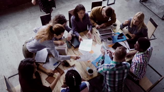vídeos de stock e filmes b-roll de business meeting at modern office. top view of multiracial group of people working near the table together. slow mo - together