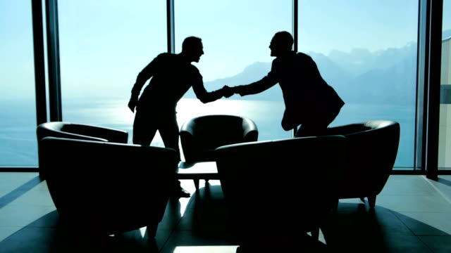 business meeting of two young entrepreneurs talking about new start up company. businessmen handshaking after sales agreement deal silhouette of two business men having a business meeting in modern office lobby hall at sunset light job interview stock videos & royalty-free footage