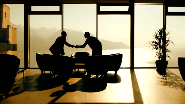 business meeting of two young entrepreneurs talking about new start up company. businessmen handshaking after sales agreement deal silhouette of two business men having a business meeting in modern office lobby hall at sunset light lobby stock videos & royalty-free footage