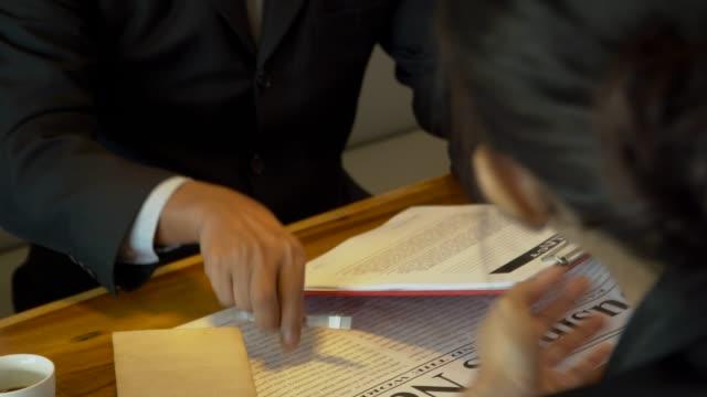 vídeos y material grabado en eventos de stock de reunión de negocios presentar y aprobar con la mano en el espacio de trabajo co - abogado
