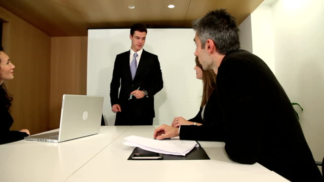 Business meeting where associate smiles at camera video