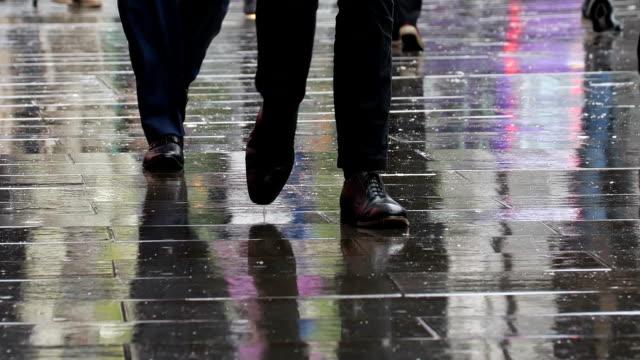 Business men walking in city rain. Lower body, legs and feet.