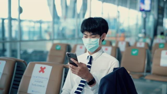 ビジネスマンは、空港にいる間、ウイルスから保護するためにマッサージを着用します。 - 乗客点の映像素材/bロール