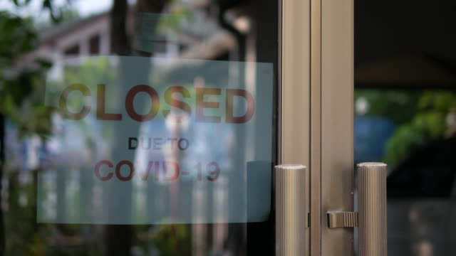 Business office or store shop is closed, bankrupt business due to the effect of novel Coronavirus (COVID-19) pandemic. Business owner person wearing medical mask placing the closed sign on front door.