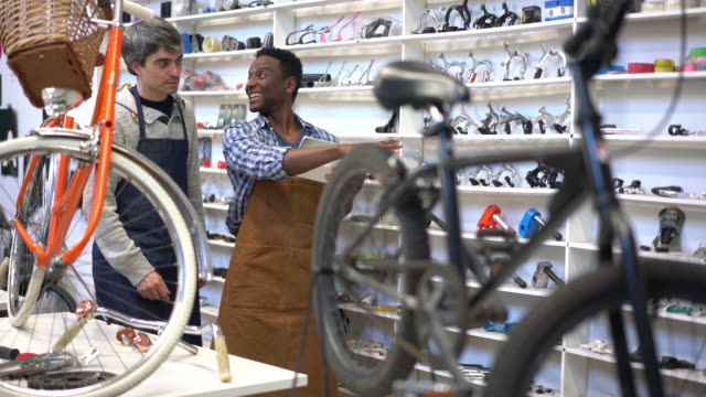Business owner and cheerful black manager going over the inventory looking at a tablet and pointing at the bicycle parts on the shelve video