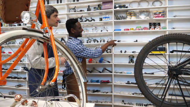 Business owner and salesman going over the inventory looking at the bicycle parts on the shelve and then looking at a tablet video