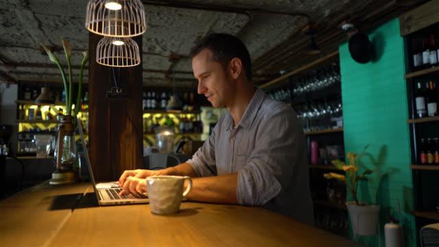 Propriétaire de l'entreprise à son restaurant travaillant sur son ordinateur portable en souriant - Vidéo