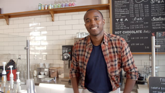 Business owner crosses arms at the counter of coffee shop video