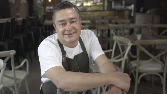 Business owner in his restaurant sitting down smiling looking at the camera