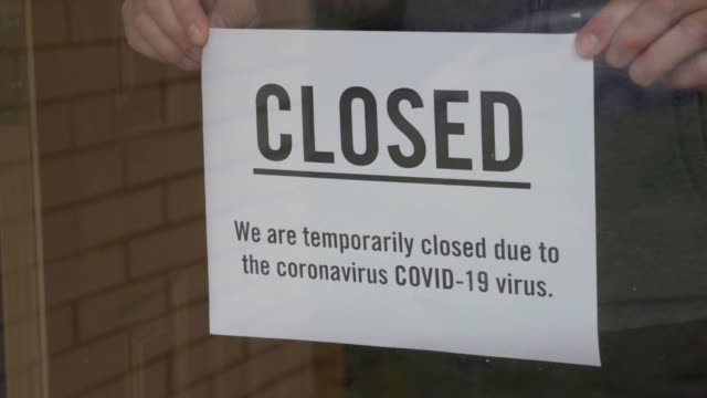 Business Owner Puts Closed Sign on Door Due to COVID-19