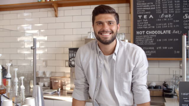 Business owner standing behind the counter at a coffee shop video