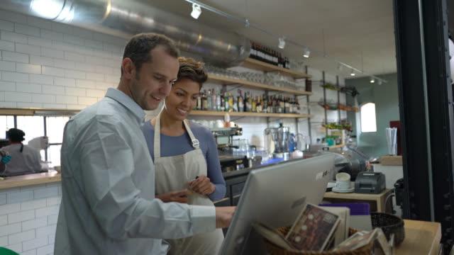 business owner training a new hire - mestiere nella ristorazione video stock e b–roll