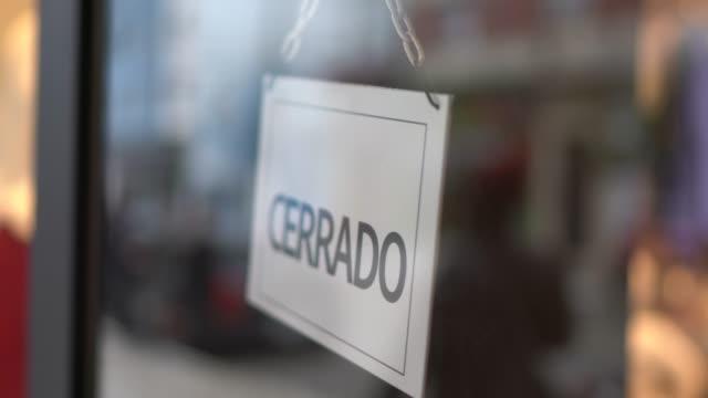 imprenditore che si rivolge al cartello chiuso (cerrado) sulla porta del negozio - hand on glass covid video stock e b–roll