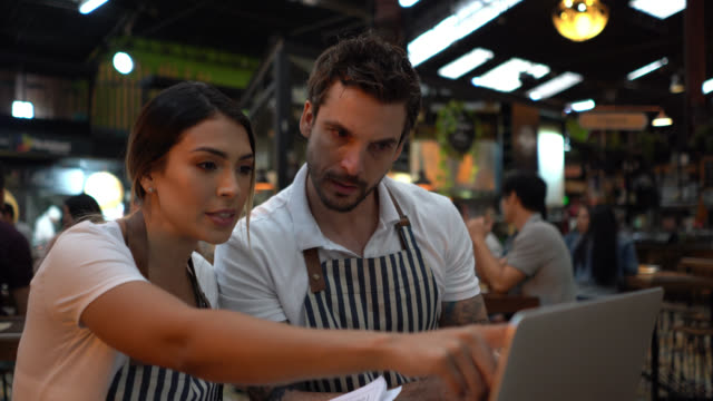 business owners of a bar doing the books talking while looking at laptop and documents - caffetteria video stock e b–roll