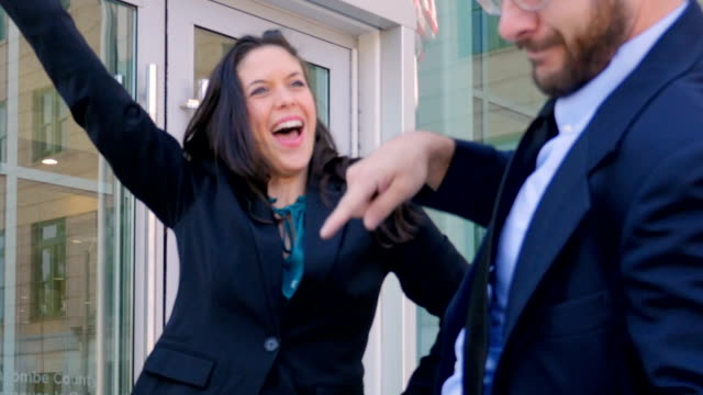 Business partners dancing and celebrating victory outside an office building