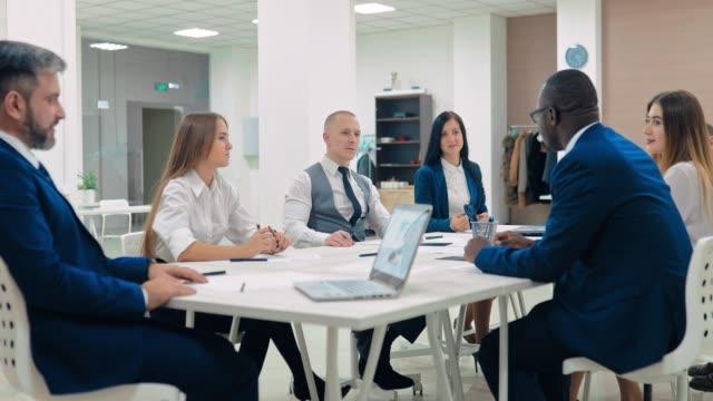 vídeos y material grabado en eventos de stock de los socios comerciales discuten los planes financieros de la empresa, el crecimiento de los beneficios. los colegas discuten las tareas estratégicas, sonriendo. juntas - planificación financiera