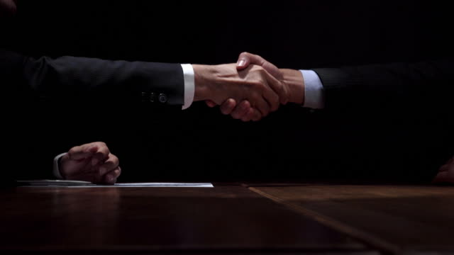 business partners making handshake after confidential meeting in dark room - mistero video stock e b–roll