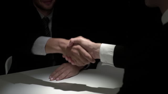 business partners making handshake in dark shadow - mistero video stock e b–roll