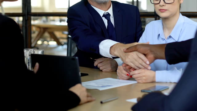 Business partners shaking hands at meeting, successfully agree to cooperate