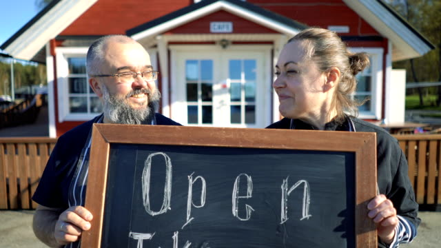 business partners standing with an open sign in front of their cafe