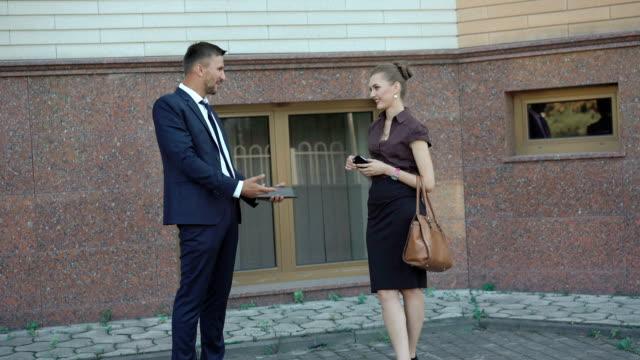 ビジネス パートナーの話と笑ってオフィスの近く。fullhd - ソーサー点の映像素材/bロール