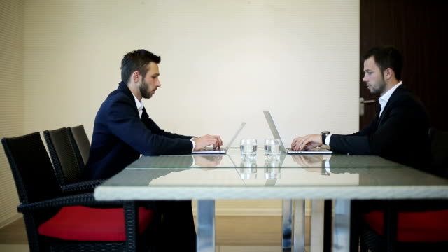 Business partners twins start working at new modern laptops video