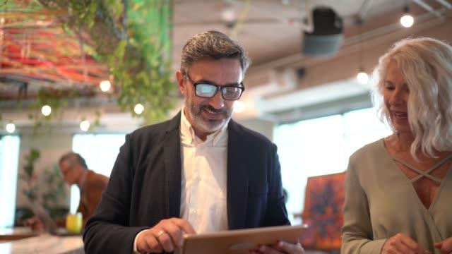 geschäftspartner beim coworking zu fuß und mit digitalem tablet - südamerika stock-videos und b-roll-filmmaterial