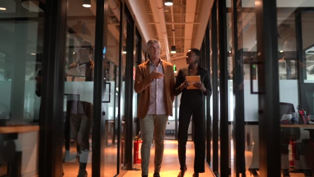 Business partners walking using digital tablet at corridor