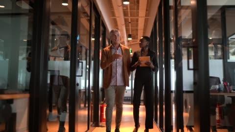 partner commerciali che camminano utilizzando tablet digitale al corridoio - due persone video stock e b–roll