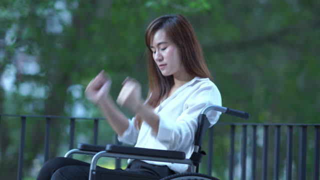 business patient woman on wheelchair , feel depressed , hitting a fist on wheelchair