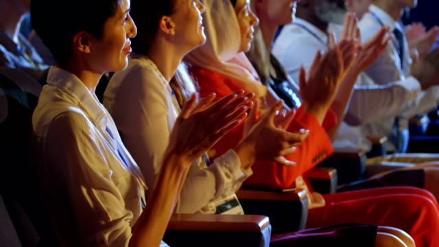 vídeos de stock, filmes e b-roll de executivos que aplaudindo ao sentar-se em assentos no auditório 4k - prêmio