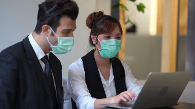 stockvideo's en b-roll-footage met zakenmensen werken aan laptop en slijtagemasker beschermen vervuiling of coronavirus - aziatische etniciteit