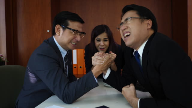 business people arm wrestling at desk in the office - wrestling stock videos and b-roll footage