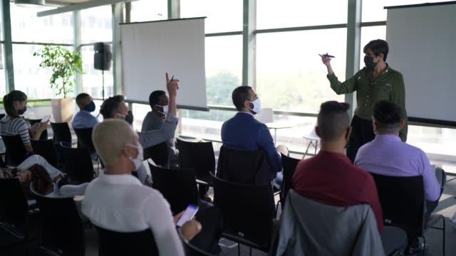 vídeos de stock e filmes b-roll de business people attending a seminar with social distancing and face mask - envolvimento dos funcionários