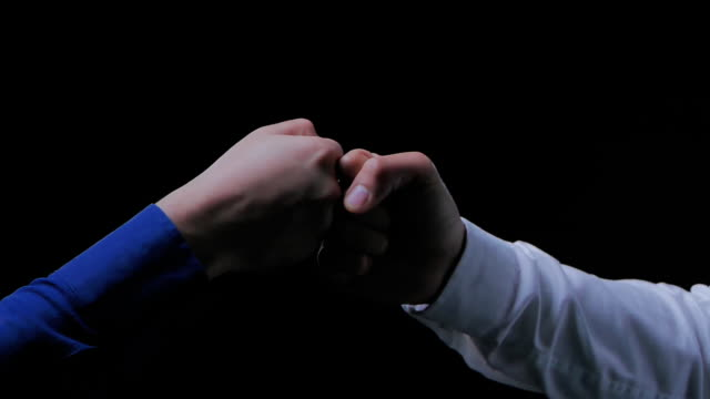Business people bump hands together,finishing up a meeting on black background.Celebration,Success,Teamwork,Collaboration,Support,Togetherness,Business etiquette,Congratulation,Merger,Acquisition concepts.Handshakes: Non-Caucasian video
