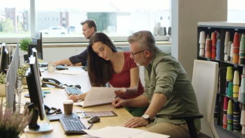 vidéos et rushes de les gens d'affaires discuter au livre au bureau - bureau ameublement