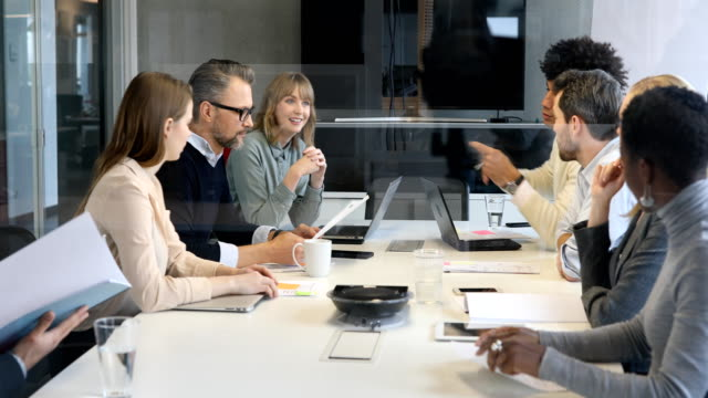 Business people discussing over document in office