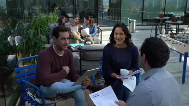 business people during meetings at the rooftop terrace looking very engaged on their work - terrazza video stock e b–roll