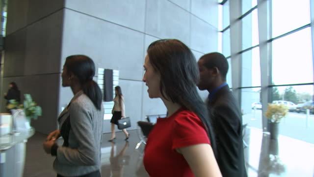 vídeos y material grabado en eventos de stock de las personas de negocios ingresar moderno edificio de oficinas - recepcionista