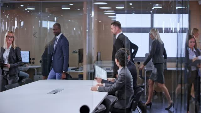 ds geschäftsleute den glas-konferenz-raum betreten und sitzen - menschliche erzeugnisse stock-videos und b-roll-filmmaterial
