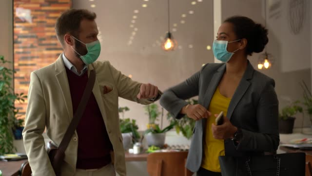business people greeting during covid-19 pandemic, elbow bump - businessman covid mask video stock e b–roll
