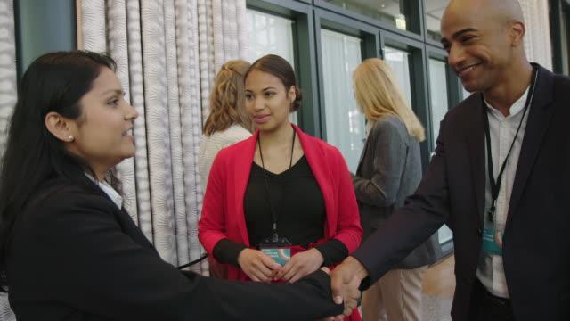 vídeos de stock e filmes b-roll de business people handshaking at convention center - funcionamento em rede
