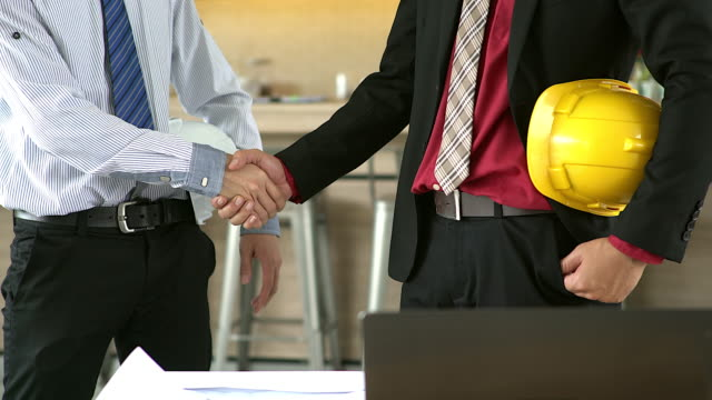 Business people handshaking demonstrating their agreement to sign agreement or contract between their firms / companies / enterprises. video