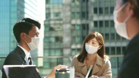 vidéos et rushes de les gens d'affaires ont une réunion avec la distanciation sociale portant le masque protecteur en asie - japon